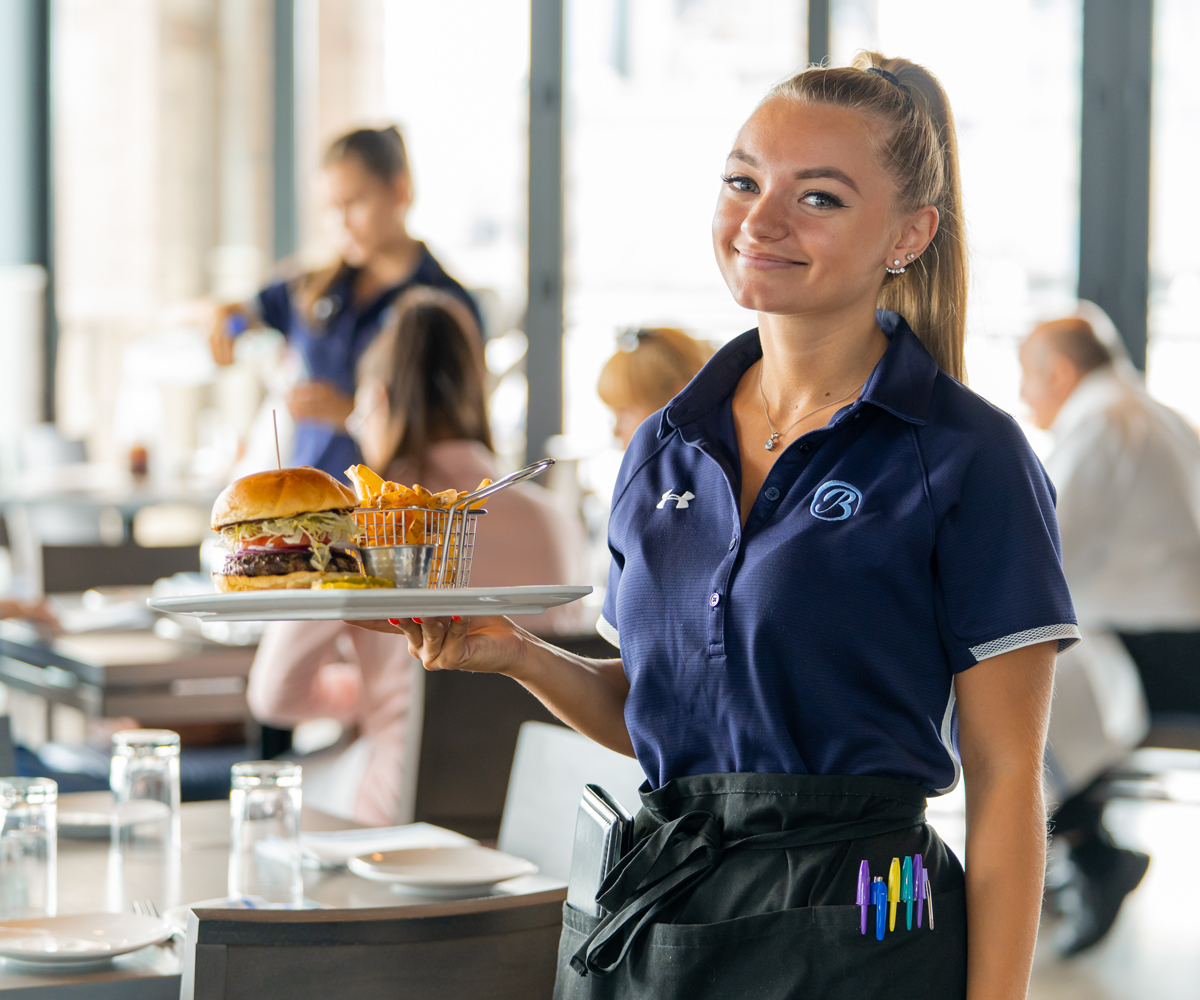 Young woman waitress holding a plate of food
