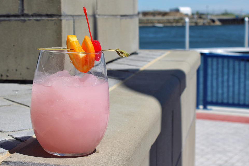 A pink mixed drink with orange and cherry garnish at Boca Oyster Bar