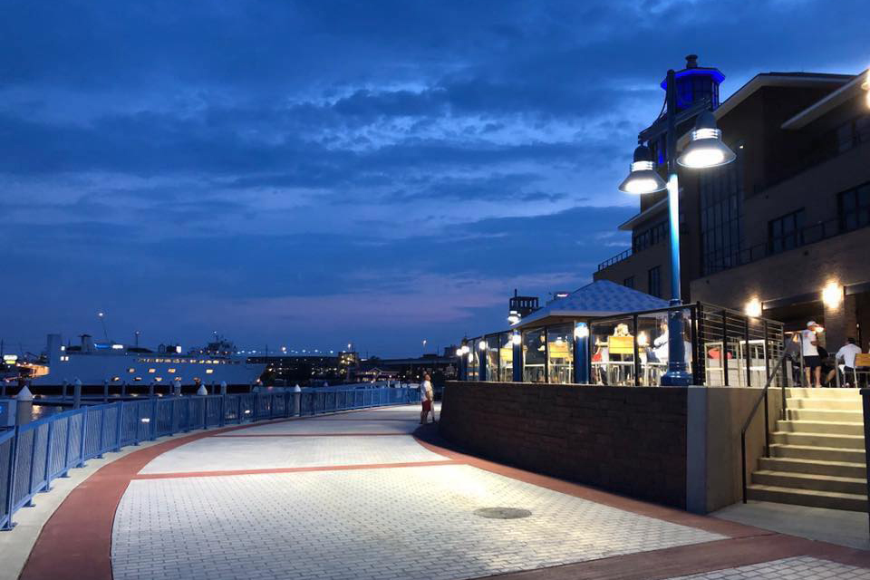 A shot at night of the walkway at Bridgeport Harbor Marina as the Bridgeport Ferry sails in