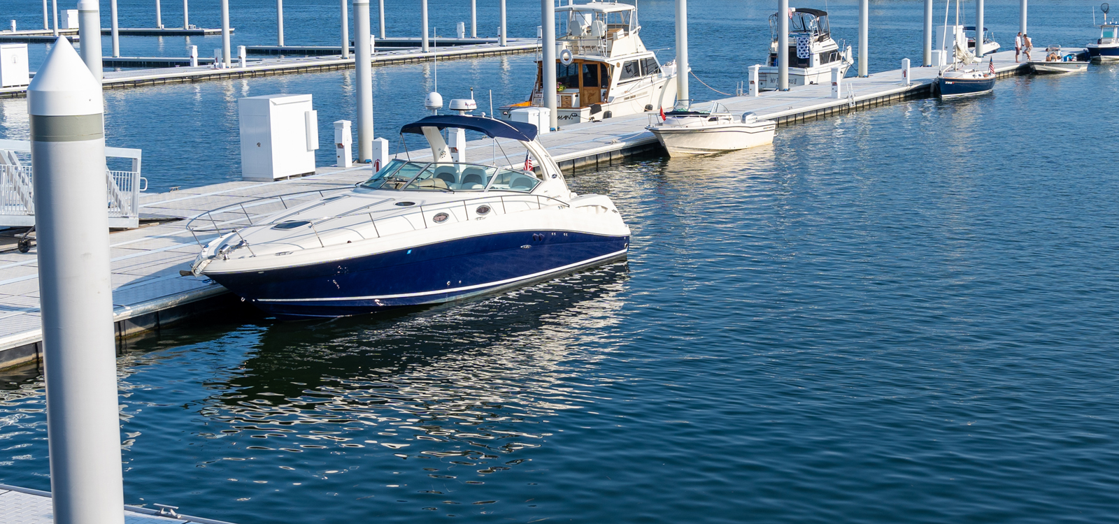 A white and blue boat docked at Bridgeport Harbor Marina
