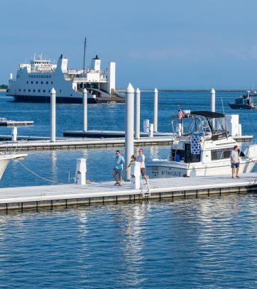 Patrons walk on the docks at Bridgeport Harbor Marina as the Bridgeport Ferry sails away