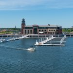 Distant view of the lighthouse at Bridgeport Harbor Marina as a boat speeds by