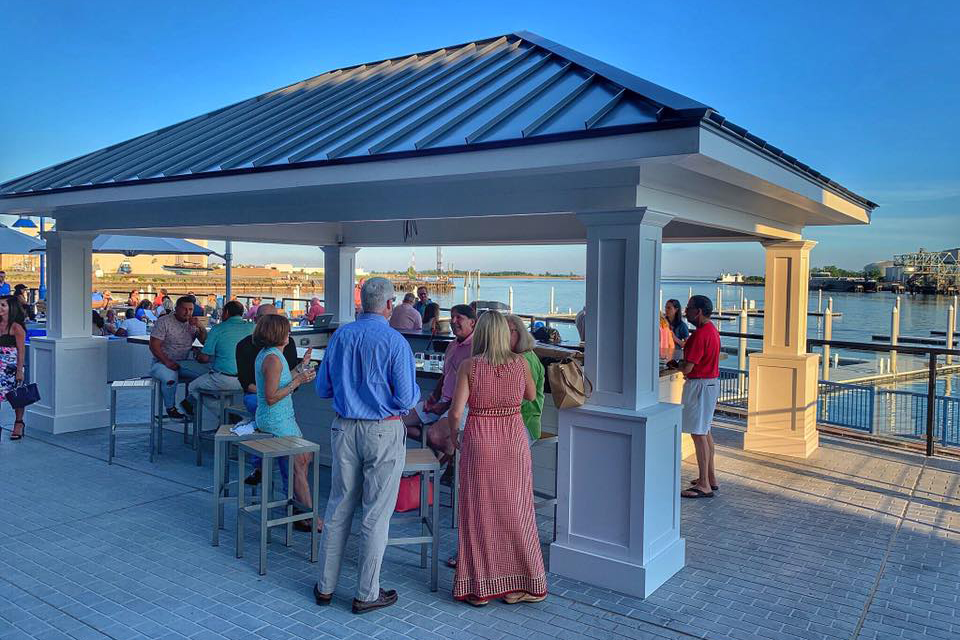 Patrons enjoying drinks by the tiki bar at Boca Oyster bar